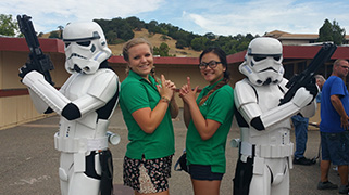 Two young women posing for a photo with two Star Wars storm troopers.